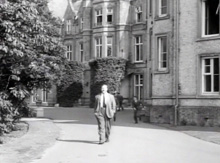 James Robertson-Justice walking from President Hall past the Clock Tower.