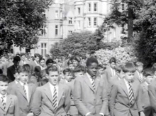 A group of schoolboys walking down the President Hall approach.